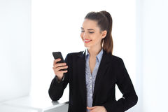 Happy business woman holding mobile phone. Happy smiling business woman holding mobile phone Royalty Free Stock Images