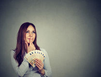 Happy business woman holding money euro banknotes in hand daydreaming. Happy successful young business woman holding money euro banknotes bills in hand looking Stock Photography