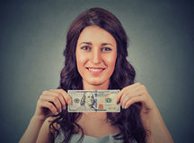 Happy business woman holding money one hundred dollar bill. Happy young business woman holding money one hundred dollar bill isolated on gray wall background Stock Photo