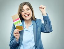 Happy business woman holding passport, credit card and ticket. Isolated portrait Stock Image