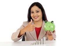 Happy business woman holding piggy bank and making thumbs up gestu Stock Image