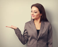 Happy business woman holding something empty in hand and demonst Royalty Free Stock Images