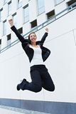 Happy business woman jumping into. The air in front of office building Royalty Free Stock Photography