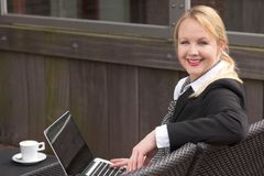 Happy business woman with laptop and cup of coffee outdoors Royalty Free Stock Photos