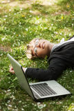 Happy business woman with laptop lying on the grass Stock Images