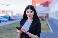 Happy business woman looking at smartphone Royalty Free Stock Photos