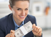 Happy business woman money pack and winking Royalty Free Stock Image