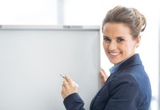 Happy business woman near flipchart. In office Royalty Free Stock Image