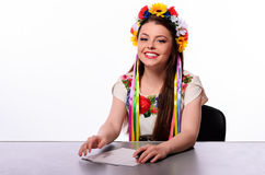 Happy business woman with note and pen by a desk In the Ukrainian national costume royalty free stock photo