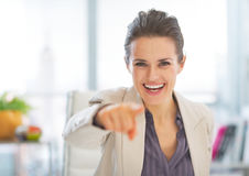 Happy business woman in office pointing in camera Royalty Free Stock Photo
