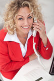 Happy business woman on the phone. In the office smiling Royalty Free Stock Photos
