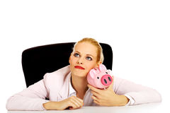Happy business woman with a piggybank behind the desk Royalty Free Stock Photo