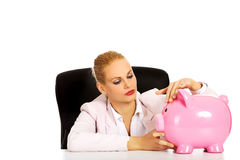 Happy business woman with a piggybank behind the desk Stock Image