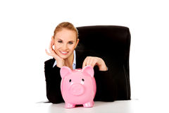 Happy business woman with a piggybank behind the desk Stock Photos