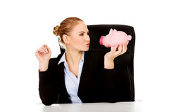 Happy business woman with a piggybank behind the desk Royalty Free Stock Photography