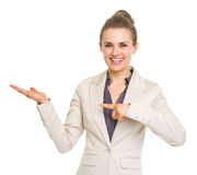 Happy business woman pointing on empty palm Stock Image