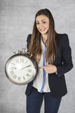 Happy business woman pointing to the hour Stock Photography