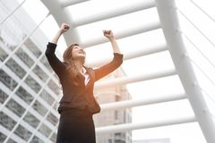 Happy business woman raise her hands at outdoors. Goal and successful concept. City and urban background royalty free stock image