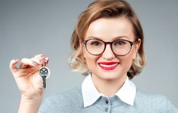 Happy business woman or real estate agent showing keys. From new house Royalty Free Stock Photos