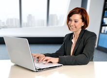 Happy business woman with red hair smiling at work typing on computer laptop at modern office desk. And sitting in front of the window at business financial Stock Photos