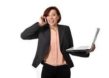 Happy business woman with red hair talking on the mobile cell phone holding laptop Stock Photo