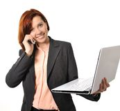 Happy business woman with red hair talking on the mobile cell phone holding laptop. In hand isolated on white background royalty free stock photos