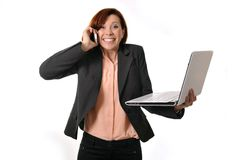 Happy business woman with red hair talking on the mobile cell phone holding laptop Stock Photos
