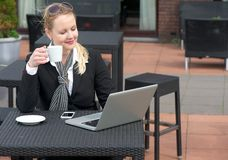 Happy business woman relaxing with a cup of coffee and looking at laptop screen Royalty Free Stock Images