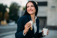 Happy business woman with sandwich and coffee. In hands, lunch outdoor. Modern building, financial center, cityscape. Female businessperson in suit at workplace Stock Photos