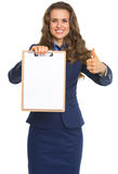 Happy business woman showing blank clipboard and thumbs up Royalty Free Stock Images