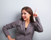 Happy business woman showing finger up on something empty on blu. E background Royalty Free Stock Photos