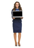 Happy business woman showing laptop blank screen. Full length portrait of happy business woman showing laptop blank screen Royalty Free Stock Image