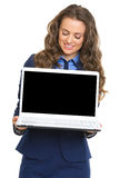 Happy business woman showing laptop blank screen. Isolated on white Stock Photos