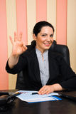 Happy business woman showing okay sign hand. Beautiful happy business woman formal wear sitting at desk in office and showing okay hand sign,check also Business Stock Photo