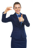Happy business woman showing small risks gesture and thumbs up Stock Photos