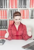 Happy business woman showing thumbs up. In office Stock Image