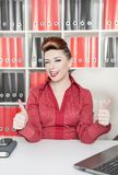 Happy business woman showing thumbs up and wink. In office Stock Photos