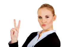 Happy business woman showing victory sign. Royalty Free Stock Image
