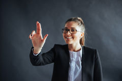 Happy business woman shows finger up, standing on a black background in the studio, friendly, smiling, focus on hand. royalty free stock photography