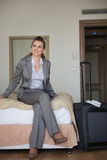 Happy business woman sitting on bed in hotel room Royalty Free Stock Images