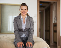 Happy business woman sitting on bed in hotel room Royalty Free Stock Photography