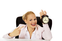 Happy business woman sitting behind the desk and holding alarm clock Royalty Free Stock Images
