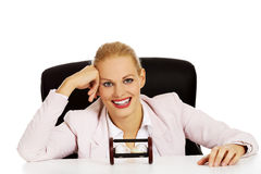 Happy business woman sitting behind the desk with sandglass Stock Images