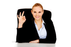 Happy business woman sitting behind the desk and shows OK sign Royalty Free Stock Images