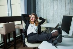 Happy business woman sitting in a boss armchair and smile. Stock Photo