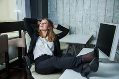 Happy business woman sitting in a boss armchair and smile. Royalty Free Stock Image