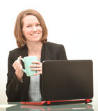 Happy business woman sitting at desk with coffee smiling Royalty Free Stock Image