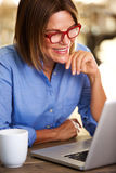 Happy business woman sitting at desk with laptop Royalty Free Stock Photos