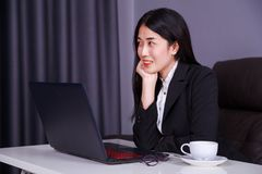 Happy business woman sitting at the desk with laptop Stock Photo