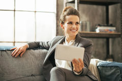 Happy business woman sitting on divan in loft. Apartment and using tablet pc Royalty Free Stock Photo